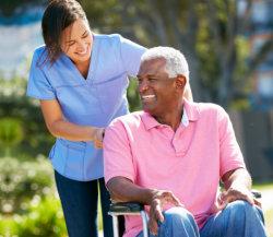 nurse guiding a senior male in wheelchair