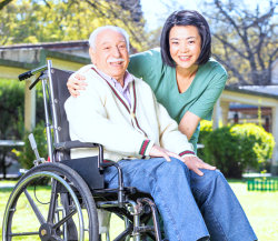 senior male in wheelchair with nurse smiling