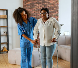 woman in crutches guided by nurse
