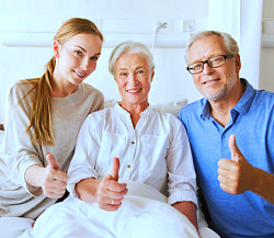 young woman and senior couple giving a thumbs up