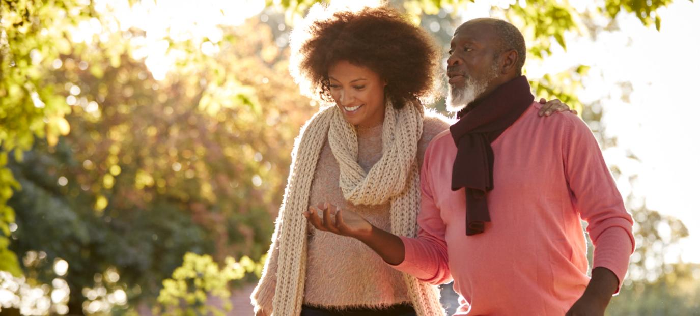 senior man and young lady walking at the park
