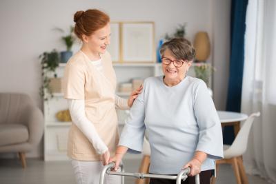 caregiver helping a senior woman on a crutch